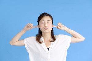 耳に指を入れる女性